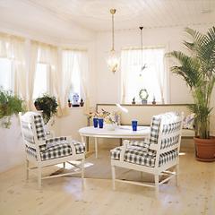 全体を白でコーディネートしたリビングルーム。爽やかなチェックのソファや観葉植物の大鉢が、リゾートの雰囲気を演出します。