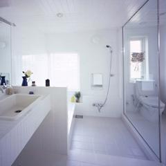ヨーロッパのホテルをイメージした白いバスルーム。トイレとの間は1枚ガラスで仕切りで、白いタイルで統一感をもたせました。洗い場には滑りにくいタイルを使用し、目地には防カビ性のあるものを用いました。