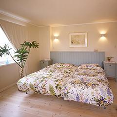 美しい木目の床材とホワイトの壁紙でコーディネートし、淡いグリーンでアクセントを加えた、ナチュラルな印象の主寝室。 朝の光が似合う爽やかな空間です。