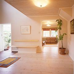 開放感をもたらす吹き抜け天井の玄関ホール。つまずき事故を防ぐために上がり框(かまち)を低くしたり、腰掛けて靴の脱ぎはきができる木製ベンチを造り付けるなど、バリアフリーに配置した設計です。